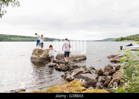 La Suède, Vastmanland, Bergslagen, Hallefors, Nygard, Famille avec quatre enfants debout sur des rochers Banque D'Images