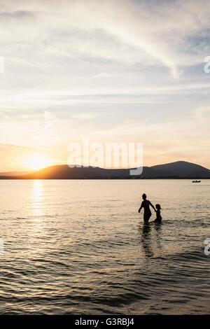 Italie, Sardaigne, Alghero, la mère et la fille de patauger dans la mer au coucher du soleil