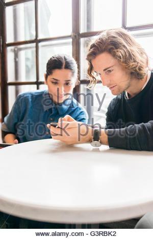 En Suède, les jeunes looking at mobile phone in cafe Banque D'Images
