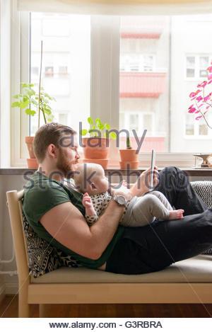 En Suède, le père holding baby boy (0-1 mois) et using digital tablet Banque D'Images