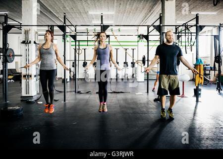 L'Allemagne, les jeunes femmes et l'homme la corde à sauter dans la salle de sport Banque D'Images