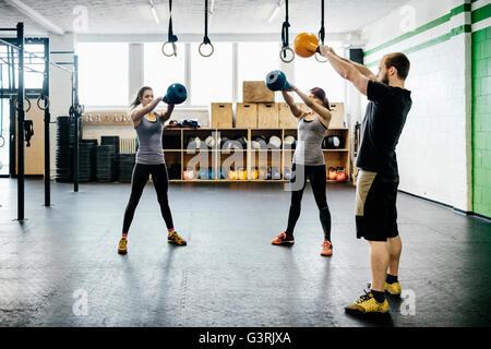 L'Allemagne, les jeunes femmes et l'homme se balançant dans sport kettlebells Banque D'Images
