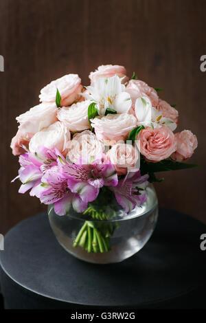 La vie encore. une table en bois anciens, vase en verre avec des belles fleurs bouquet. Banque D'Images