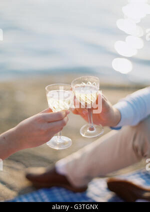 La Suède, Sweden in Kitchen, Couple toasting with champagne glasses on sandy beach Banque D'Images