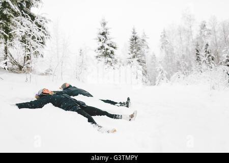 La Finlande, Jyvaskyla, Saakoski, jeune couple making snow angel Banque D'Images