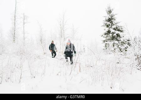 La Finlande, Jyvaskyla, Saakoski, jeune couple en train de marcher parmi les arbres nus en hiver Banque D'Images