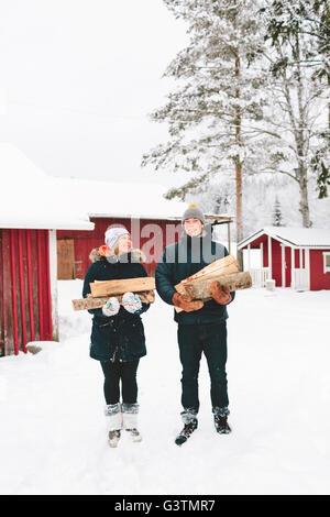 La Finlande, Jyvaskyla, Saakoski, Young couple holding et bois de chauffage avec maisons en arrière-plan Banque D'Images