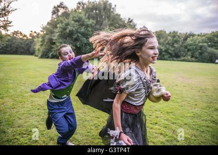 Enfants chase une fille habillé comme un zombie prom queen pour l'Halloween. Banque D'Images