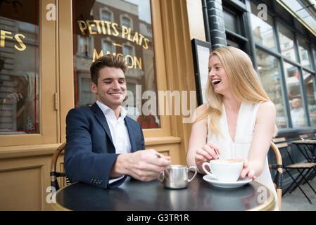 Deux amis assis à l'extérieur d'un café dans le quartier de Covent Garden à Londres. Banque D'Images