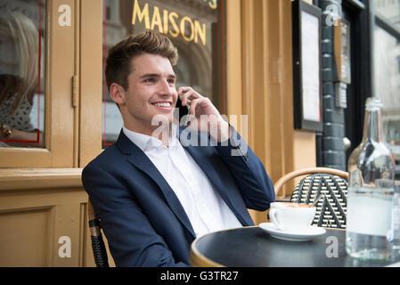 Un homme femme assise à l'extérieur d'un café sur le téléphone à Covent Garden à Londres. Banque D'Images