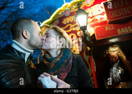 Un couple s'embrasser devant un vendeur vente de marrons chauds sur la rive sud de Londres la nuit. Banque D'Images