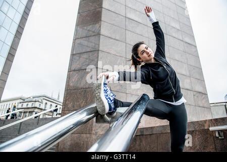 Une jeune femme de souplesse avant un jogging le long de la rive sud de Londres. Banque D'Images
