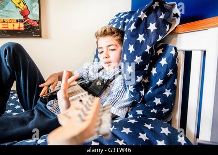 Un garçon de dix ans portant sur son lit, jouant de la guitare. Banque D'Images