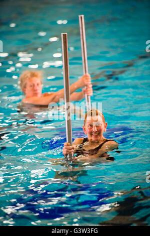 """Hydropole piscine salle classe: un groupe de jeunes adultes adultes hauts femmes prenant part à un """"hydropole' pole dancing Cours de conditionnement physique dans l'eau dans une piscine, UK"""