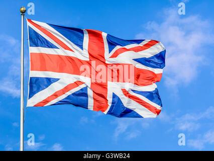 Union Jack flag du Royaume-Uni de Grande-Bretagne et d'Irlande du Nord, battant sur un poteau contre le ciel bleu. Banque D'Images