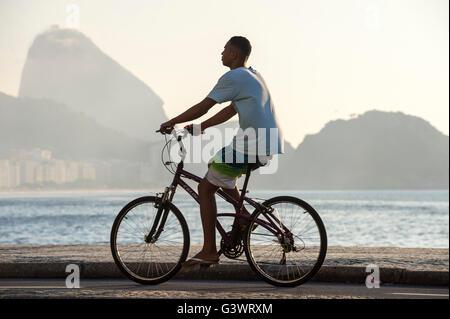 RIO DE JANEIRO - le 3 avril 2016: Jeune homme brésilien monte un vélo sur la promenade à bord de la plage de Copacabana. Banque D'Images