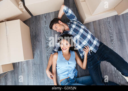 Portrait of young smiling happy couple moving in new home Banque D'Images
