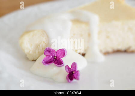Cheesecake citron décoré avec des fleurs lilas. Profondeur de champ intentionnel avec l'accent sur la fleur de lilas. Banque D'Images