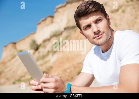 Portrait of handsome young man with tablet sur la plage