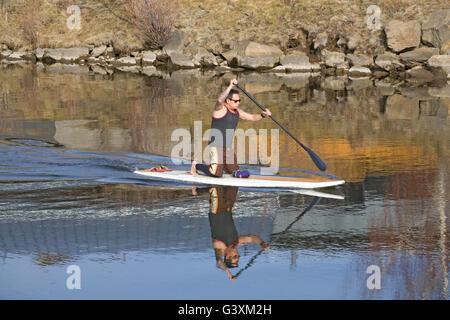 Tattooed man à genoux sur un paddleboard standup. Banque D'Images