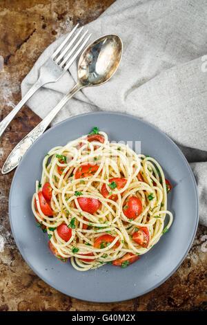 Les pâtes Spaghetti aux tomates cerises et le persil sur arrière-plan rustric Banque D'Images