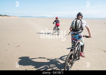 Randonnée à vélo le long d'une partie de 8kms de long vide Pembrey Sands Beach sur un dimanche ensoleillé de juin. Banque D'Images