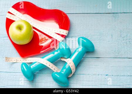 Mettre en place et de la santé concept abstrait avec coeur rouge Plaque sur fond bleu en bois Banque D'Images