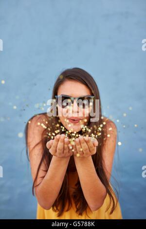 Portrait of happy young female model blowing confetti dans l'air au-dessus de l'arrière-plan lumineux Banque D'Images