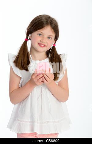 Petite fille l'écoute de musique au casque sur un smartphone. Elle sourit à la caméra et se tenir contre un bac Banque D'Images