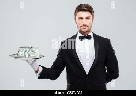 Beau jeune garçon in tuxedo debout et tenant de l'argent sur le bac