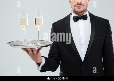 Libre de deux verres de champagne sur le plateau retenus par handsome waiter in tuxedo Banque D'Images