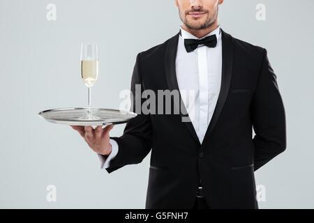 Beau jeune garçon en smoking et noeud papillon debout et tenant le bac avec un verre de champagne