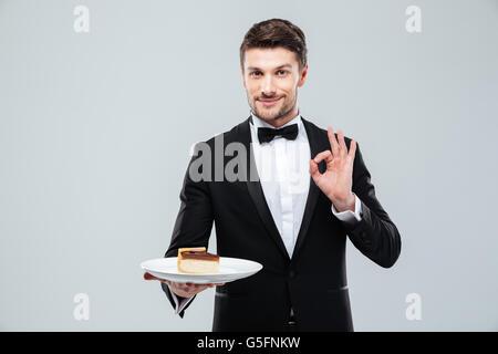 Beau jeune garçon en smoking avec nœud papillon maintenant la plaque avec du gâteau et montrant ok sign