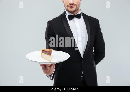 Gros plan du jeune serveur in tuxedo holding piece of cake on plate
