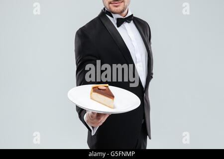 Butler in tuxedo avec bowtie maintenant la plaque avec du gâteau