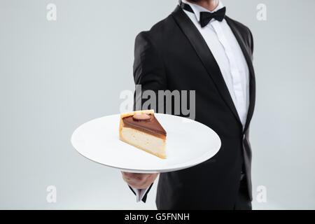 Waiter in tuxedo avec bowtie maintenant la plaque avec du gâteau