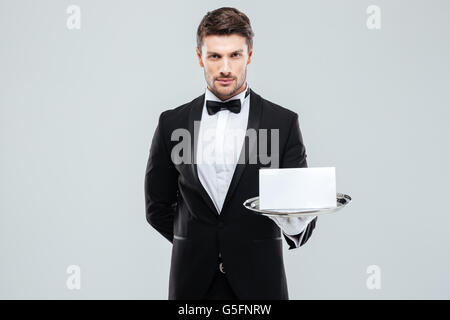 Confiant dans Butler tuxedo holding blank card on tray