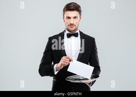 Beau jeune garçon in tuxedo holding tray with carte vierge
