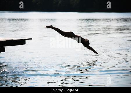 Femme de sauter dans le lac Banque D'Images
