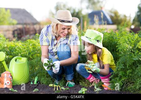 Mère et fille enfant la plantation des semis de fraises en été