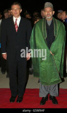 Le Premier ministre britannique Tony Blair (L) se tient avec le chef intérimaire afghan Hamid Karzaï (R) à son arrivée à la base aérienne de Bagram. M. Blair s'est envolé pour l'Afghanistan lundi, devenant le premier chef de gouvernement occidental à se rendre dans le pays depuis la chute du régime taliban.