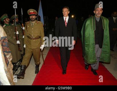 Le Premier ministre britannique Tony Blair (L) marche avec le dirigeant intérimaire afghan Hamid Karzaï (R) à son arrivée à la base aérienne de Bagram. M. Blair s'est envolé pour l'Afghanistan lundi, devenant le premier chef de gouvernement occidental à se rendre dans le pays depuis la chute du régime taliban.
