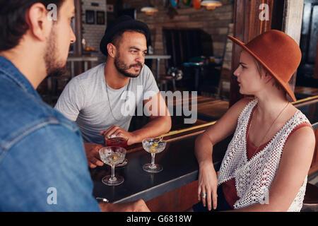 Groupe de jeunes amis assis et parler dans un café. Les jeunes hommes et de femmes réunis dans un café et discuter. Banque D'Images