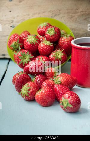 Les fraises éparpillés dans bol vert et avec le jus dans la coupe d'argile rouge sur bleu table en bois avec mur Banque D'Images