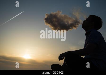 Silhouette of man fumant une pipe à Cap au coucher du soleil. Photographe à une casquette de baseball fumant une pipe au coucher du soleil par la mer.Travel, adventure, méditation, relaxation, vacances.
