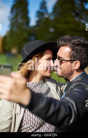 Couple in love en tenant avec smartphone selfies Banque D'Images