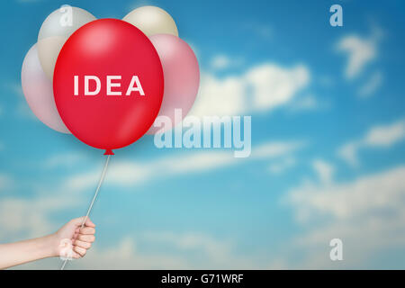 Hand Holding idée Balloon avec sky fond flou Banque D'Images