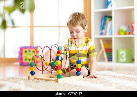 Bambin enfant jouant avec des jouets colorés. Enfant jouant avec des jouets en bois à la maternelle ou garderie. Banque D'Images