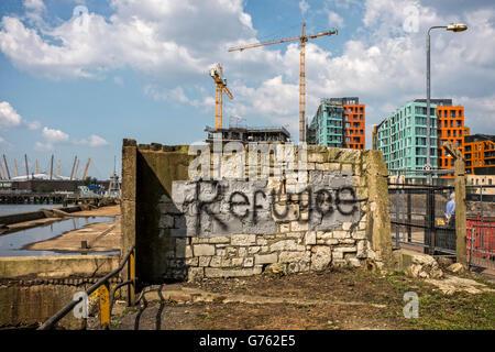 Les graffitis sur vieux mur en face de Barratt's Enderby Wharf développement d'appartements de luxe et de Croisière Banque D'Images