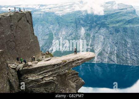 Odda, Norvège - Août 04, 2014: Les jeunes sont photographiés debout sur un rocher Trolltunga - Langue de Troll Banque D'Images